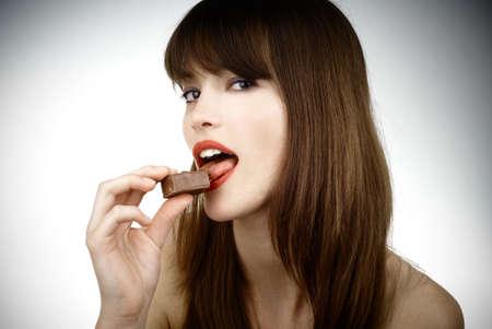 beautiful woman biting a bar of chocolate in a sexy way