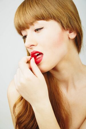 beautiful red hair woman eating a red candy photo