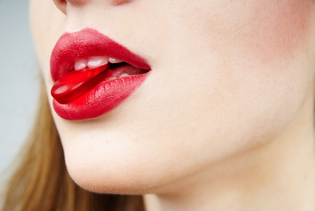 close up of womans lips with a red candy photo
