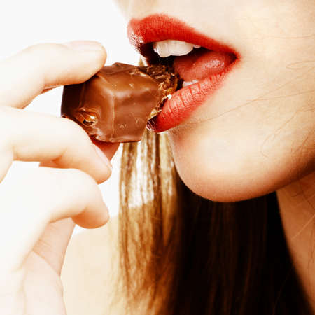 close up of womans lips biting a chocolate bar photo