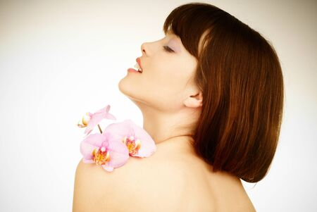 relaxed woman with a pink orchid on her back photo
