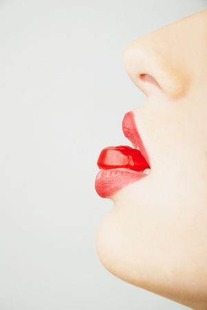 woman's lips biting a red candy photo
