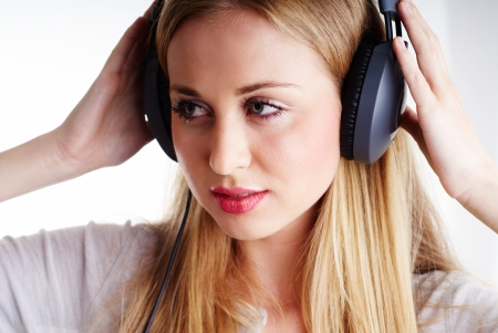 nice blond woman listening to the music on headphones
