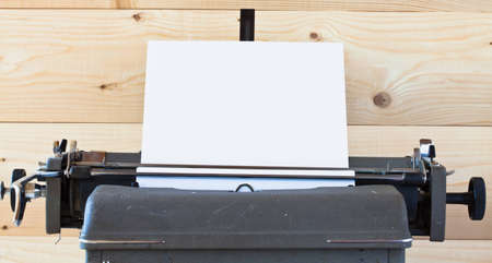 The old typewriter with a sheet of paper against a wooden wall Stock Photo - 7946245