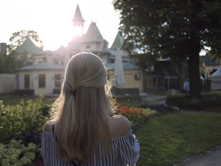 a blonde woman enjoys the sunset in Sweden
