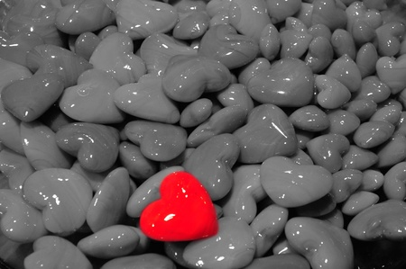Red polished heart shaped stone among other gray hearts photo