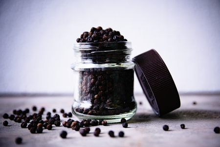 piperine: Spicy peppercorns in a glass jar on a wooden background.