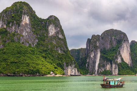 Halong bay limestone cliffs with a Vietnamese traditional green fishing boat Banco de Imagens