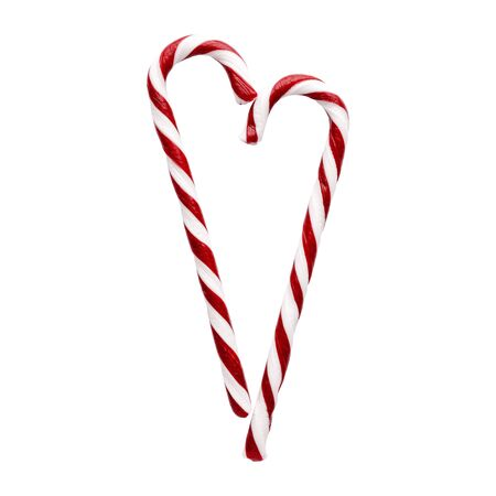 Heart shape made with Christmas candy canes isolated on white background. Red and white striped peppermint candies