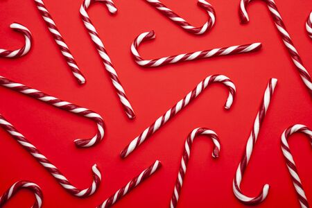 Pattern made with Christmas candy canes on red background. Minimal composition with red and white striped peppermint candies. Top view