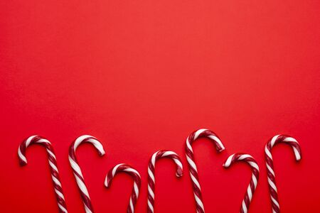 Frame made with Christmas candy canes on red background. Minimal composition with red and white striped peppermint candies. Top view with space for text
