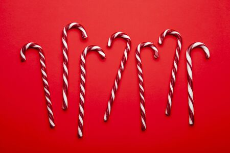 Christmas candy canes on red background. Minimal composition with red and white striped peppermint candies. Top view