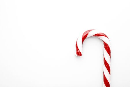 Christmas candy cane on white background. Minimal composition with peppermint candy. Top view with space for text