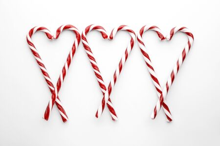 Christmas candy canes on white background. Minimal composition with peppermint candies. Top view with