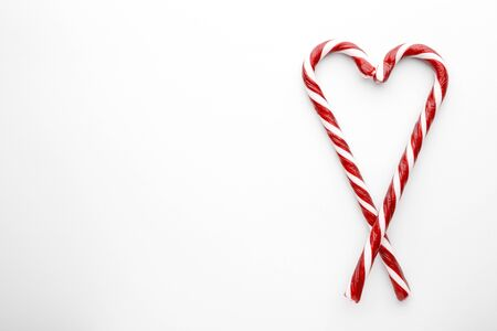 Heart shape made with Christmas candy canes on white background. Minimal composition with peppermint candies. Top view with space for text