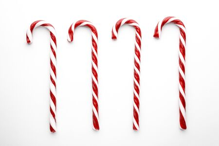 Christmas candy canes on white background. Minimal composition with peppermint candies. Top view 版權商用圖片