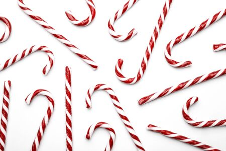Pattern made with Christmas candy canes on white background. Minimal composition with peppermint candies. Top view