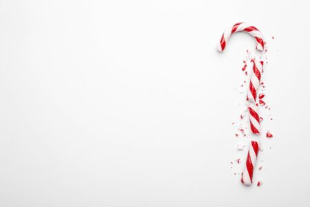 Broken Christmas candy cane on white background. Minimal composition with peppermint candy. Top view with space for text