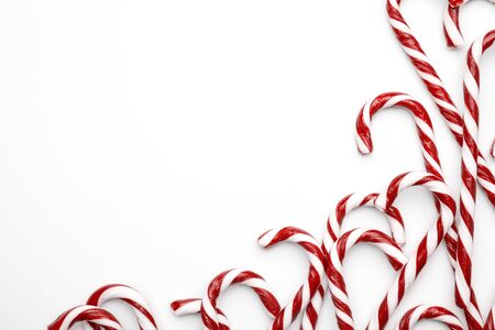 Frame made with Christmas candy canes on white background. Minimal composition with peppermint candies. Top view with space for text 版權商用圖片