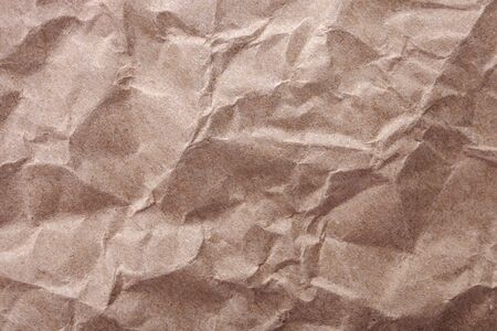Crumpled brown craft paper texture as background. Top view with place for text 版權商用圖片