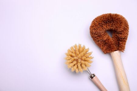 Wooden brushes for cleaning on white background. Zero waste concept. Top view with place for text