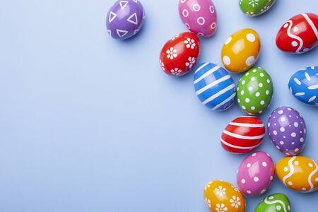 Flat lay composition with Easter eggs on color background. Frame made of decorated eggs. Top view with place for text