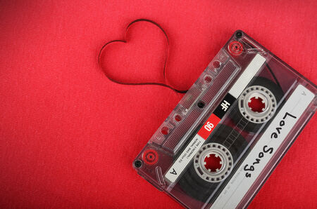 Vintage audio cassette with loose tape shaping a heart 스톡 콘텐츠