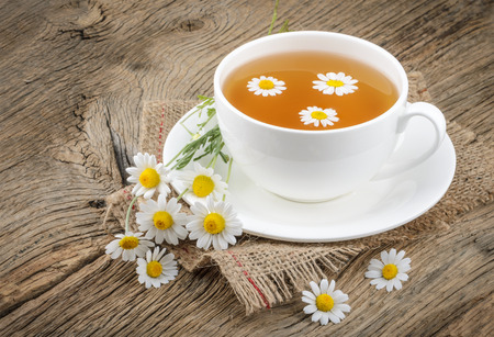 chamomile tea: Cup of tea and chamomiles on wooden background