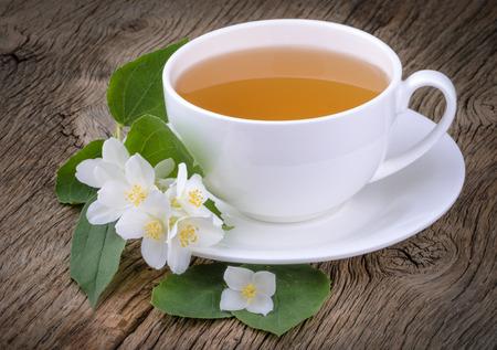 Чашка зеленого чая с цветками жасмина на деревянном фоне