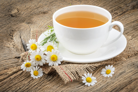 Cup of tea and chamomiles on wooden background