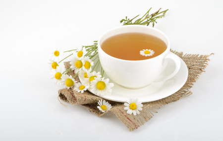 chamomile tea: Cup of tea and chamomiles Stock Photo