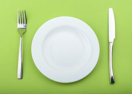plato de comida: plato vacío, tenedor y cuchillo sobre fondo verde Foto de archivo