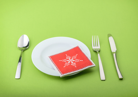 isolated  on white: Plate fork and knife in a christmas napkin