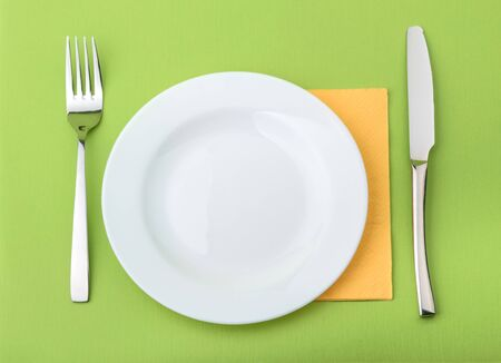 Empty plate, fork and knife on green background