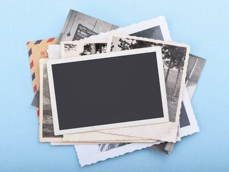 Pila di vecchie foto su sfondo blu Archivio Fotografico