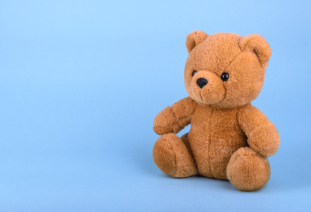 Toy teddy bear on blue background with copy space Stock Photo