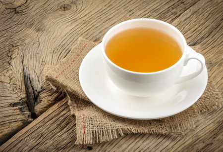 warm drink: Cup of tea and chamomiles on wooden background