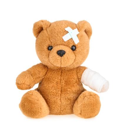 Teddybeer met verband op wit wordt geïsoleerd