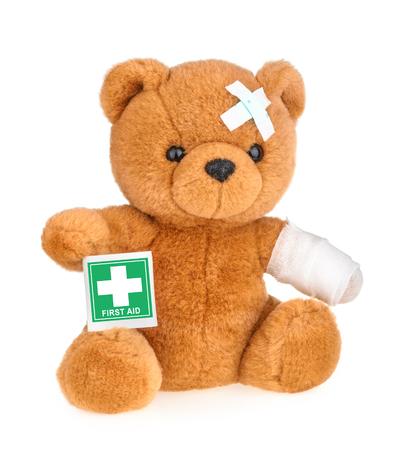Teddybeer met verband op wit wordt geïsoleerd Stockfoto