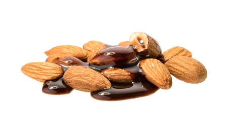 Het gieten van gesmolten chocolade en amandel noten geïsoleerd. zonder schaduw