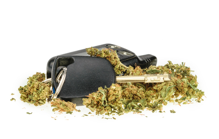 Driving high, marijuana and car key isolated on white