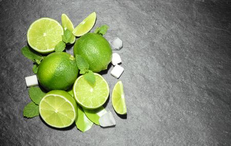 lemon slice: Limes and mint on stone background. Top view with copy space
