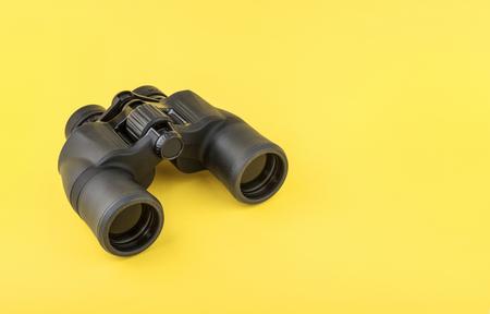 Binoculars on yellow background Imagens