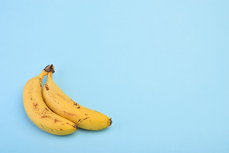 Bananas on blue background top view