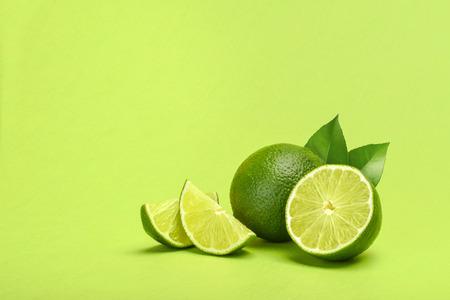 Limes on green background copyspace Reklamní fotografie