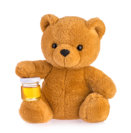 Teddy bear holding honey pot isolated white background