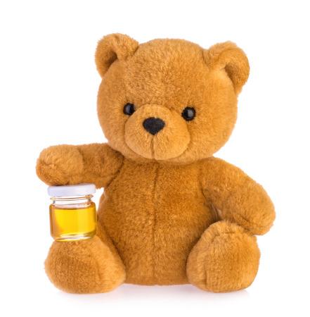 Teddybär mit Honigtopf isoliert auf weißem Hintergrund