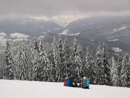 skiers in ski suits are sitting on the snow. resting on the top of the mountain