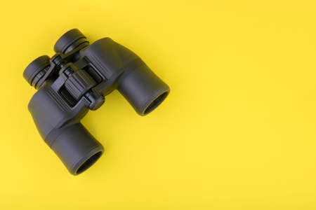 Binoculars on yellow background top view