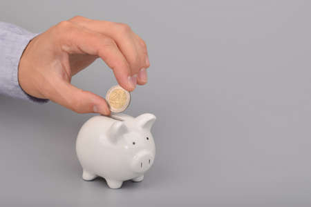 Hand holding coin. Piggy bank money savings concept
